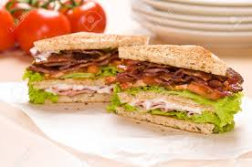bacon wrapping paper two sandwich on wrapping paper back ground has tomatoes and dishware