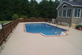 pool design with patio concrete resurfacing between fence and