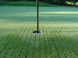 the high maintenance of a natural putting green synthetic turf