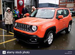 jeep mini family taking a test drive in a 2016 omaha orange jeep renegade