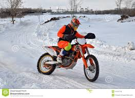 snow motocross bike racer motorcycle rides on snow covered road stock photo image