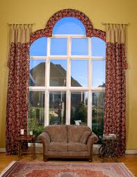 custom window treatment for large arched window and brown couch