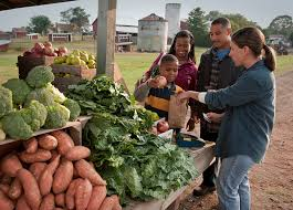 a family purchases produce from a farmers market vendor snap ed