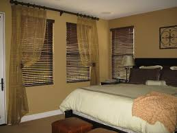 light brown master bedroom with three section window using dark f