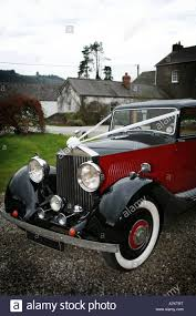 red and vintage rolls royce wedding car with typical