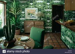 green tropical leaf wallpaper in dining room with cactus on table