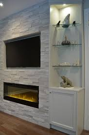 one end of fireplace wall with custom cabinetry erthcoverings silver fox stone and dimplex