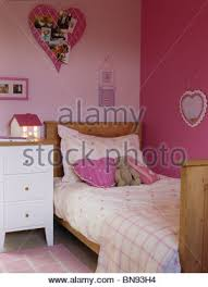Pink Bedroom Cushions - pink throw and cushions on bed with upholstered grey headboard in