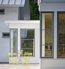 dark gray window trim patio farmhouse with white vinyl siding