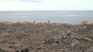 man sitting on the edge of a cliff and fishing stock footage video
