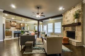 a stone fireplace and rustic wood beams define this great room and