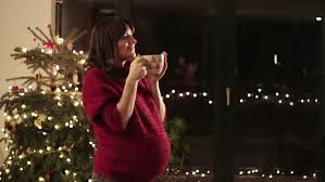 happy young pregnant woman standing near the christmas tree and