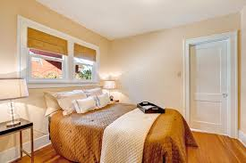 warm bedroom interior with brown bedding and ivory blanket stock