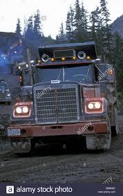 excavator and dump trucks working on new mine road bc canada