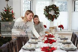 christmas dinner table setting mother and daughter setting the table for christmas dinner stock