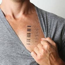 men show piano keys tattoo design with letters make on chest