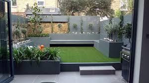 modern small low maintenance garden fake grass grey raised beds