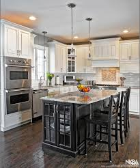 kitchen with black island and white cabinets black island surrounds by antique white cabinets nkba