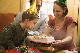 caucasian boy in party hat blowing out candles on birthday cake