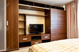 comfortable bedroom with tv and wardrobes stock photo picture and
