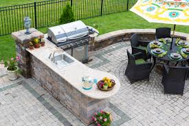 outdoor kitchen and dining table on a paved patio hive