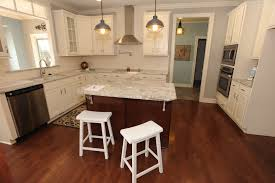 kitchen style island has grey granite countertop under pendant