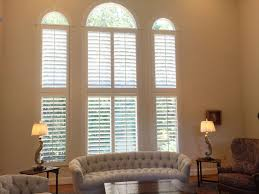 plantation shutters with an eyebrow arch specialty shaped window