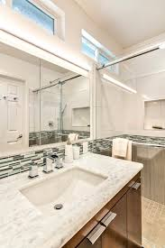 neutral floor tile and vertical gray half wall tile in the shower