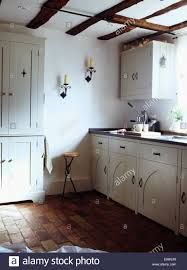 old brick flooring in white country cottage kitchen stock photo