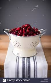 bright red cranberries in a cream colored strainer sitting on a bright red cranberries in a cream colored strainer sitting on a vintage striped linen on butcher block
