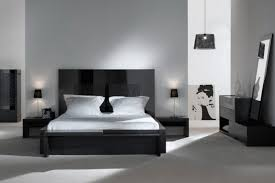 black and white bedroom wooden flooring grey headboard bed