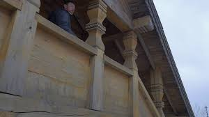 man walking downstairs by carved wooden staircase traditional