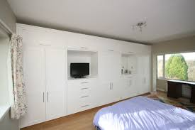 rank of bespoke wardrobes with tv and mirror alcoves cupboards