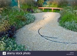 gravel path leading to a wooden bench seat edged with borders