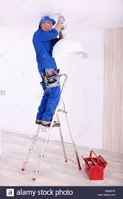 Hanging A Ceiling Light Electrician Hanging A Ceiling Light Stock Photo Royalty Free