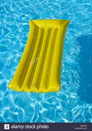 lilo inflatable air bed mattress in a swimming pool stock photo