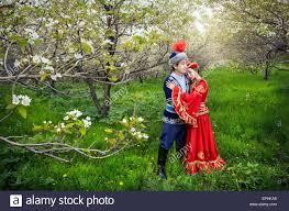 couple in kazakh costume in spring blooming apple garden of almaty