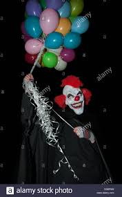 clown baloons a scary clown holding balloons against a black background stock