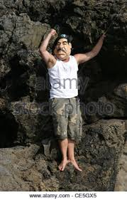 saddam hussein hanging onto rocks at the beach stock photo