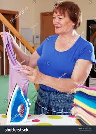 elderly woman clothes elderly woman ironing clothes on ironing stock photo 306577682