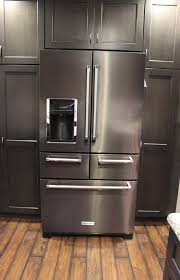gray kitchen cabinets with black stainless steel appliances durasupreme peppercorn kitchen with cambria tops and black