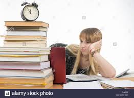 Picture Of Student Sitting At Desk Sad Student Sitting At A Desk With A Large Stack Of Books And