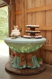 wooden spool with icicle lights covered with round table cloth