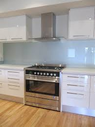 white gloss glass kitchen cabinets pale blue glass splash back in the kitchen the white