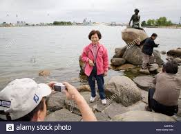 japanese tourists take photos of the little mermaid statue in