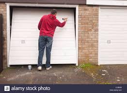 a model released man doing diy painting a garage door in the uk