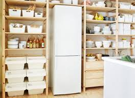 ivar pantry wooden shelving units built around fridge and containing crockery
