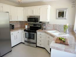 marble countertops painted white kitchen cabinets lighting