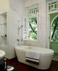 32 pictures of incredible bathrooms by top interior designers rich hardwood flooring contrasts with white marble around the soaking tub and in the shower enclosure
