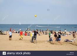 guys playing basketball on the beach in barcelona spain stock